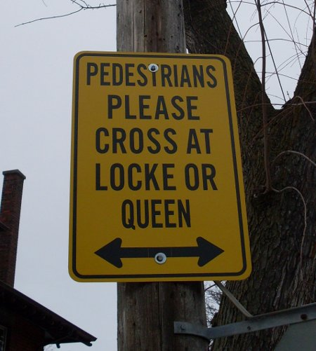 Posted sign at Aberdeen and Kent: 'PEDESTRIANS PLEASE CROSS AT LOCKE OR QUEEN'