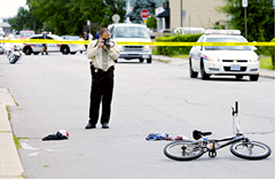 A police officer investigates the fatal cycling collision on Glow Avenue (Photo Credit: Barry Gray, Hamilton Spectator)