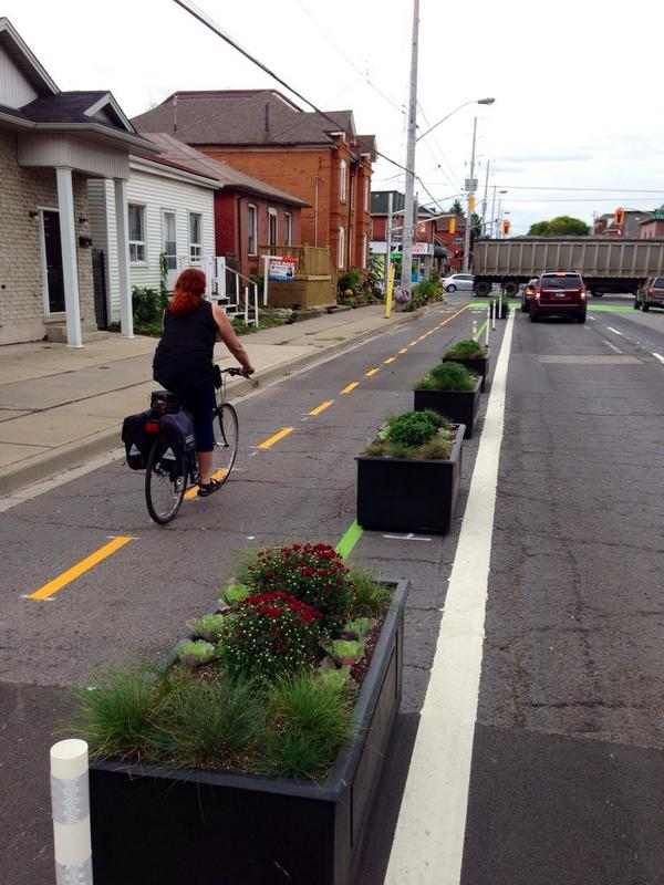 Cyclist riding past the Canon Cycle Track planter boxes (Image Credit: Jason Leach)