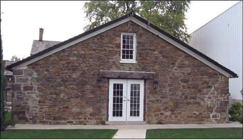 Figure 3. Cottage on the E.D. Smith property, Winona. Built as a farm building in 1835. The stone is local fieldstone, mostly Silurian Grimsby sandstone derived from the Niagara escarpment. The worn shapes are evidence that it was not derived from a quarry.