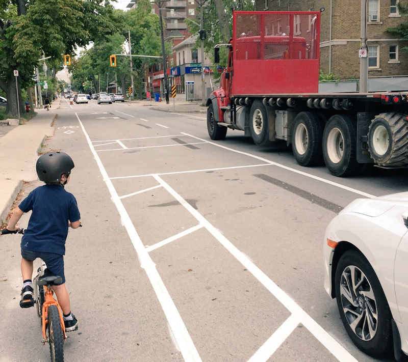 A child rides in the protected bike lanes on Herkimer while a transport truck drives past (Image Credit: Tom Flood)