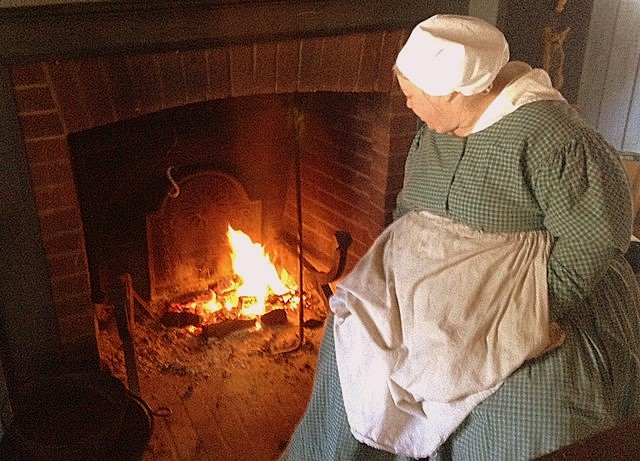 A log cabin mistress tends a warming fire.