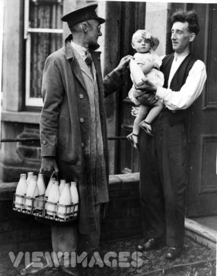 Circa 1935: A milkman chats with a father holding a baby, as he leaves the daily quota of milk on the doorstep. (Photo by Fox Photos/Getty Images)