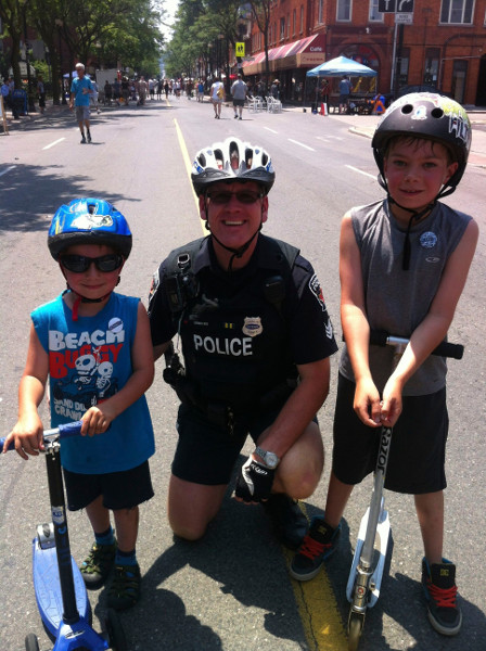 Police officer with two young scooterers