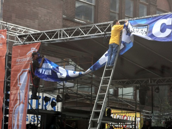 Stage crew hang the SUPERCRAWL banner