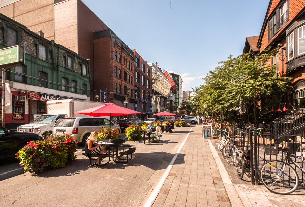 John Street, Toronto with a lane blocked by planters for tables and chairs (Image Credit: Torontoist)