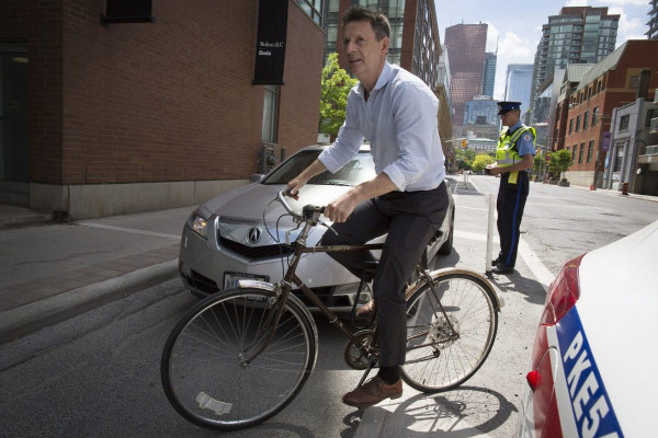 Ben Bull weaving around a car blocking the Adelaide bike lane as a police officer issues a ticket (Image Credit: Todd Korol/Toronto Star)