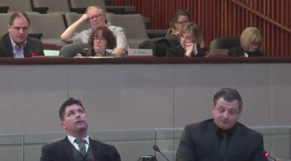 Councillor Collins, bottom left, continues to roll his eyes slowly as Paul Johnson, top left, responds to a question from Councillor Merulla, bottom right (Image Credit: screen capture from TPR video)