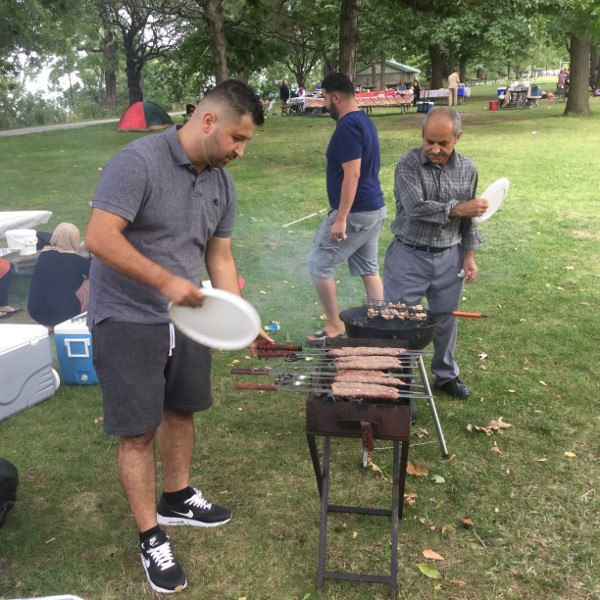This family was originally from Tajikistan and made their way to Canada via Greece and then Quebec, and now reside on Hamilton Mountain. The gentleman is barbecuing kebabs. The women were nearby on the ground preparing the meat.